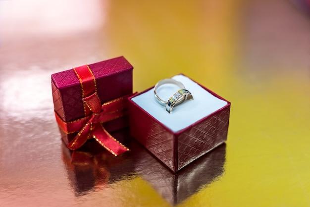 Alianças em caixa de presente vermelha em fundo dourado