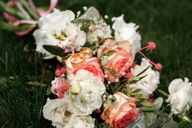 Alianças em close-up do buquê da noiva