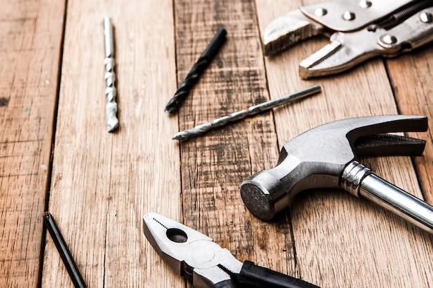 Alicate de aço e ferramenta de carpinteiro de martelo em fundo madeira