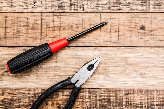 Alicate e ferramenta de carpinteiro de martelo em fundo madeira