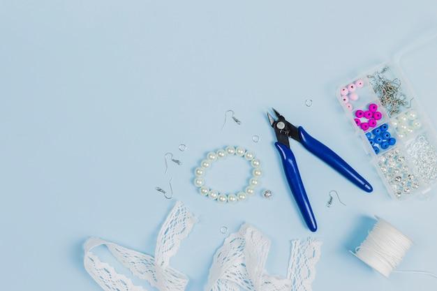 Alicate; gancho; pérolas; fita de renda; carretel de fio e caixa de grânulos de plástico no fundo azul