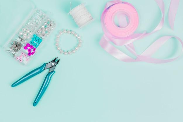 Alicate; pérolas; carretel de fio e fita rosa em fundo verde-azulado