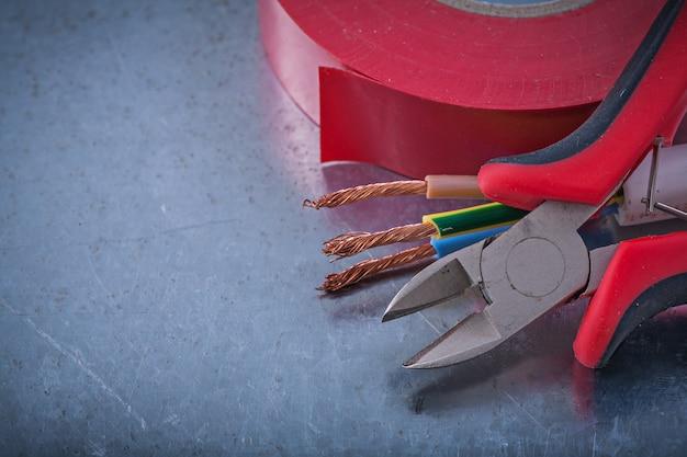 Alicates de fita isolante pinças fios elétricos na mesa metálica, conceito de construção