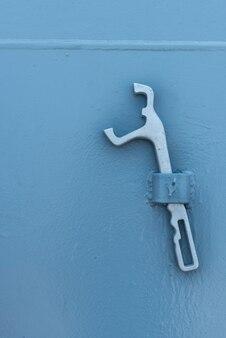 Alicates de metal prata no fundo da parede. os alicates penduram na parede branca.