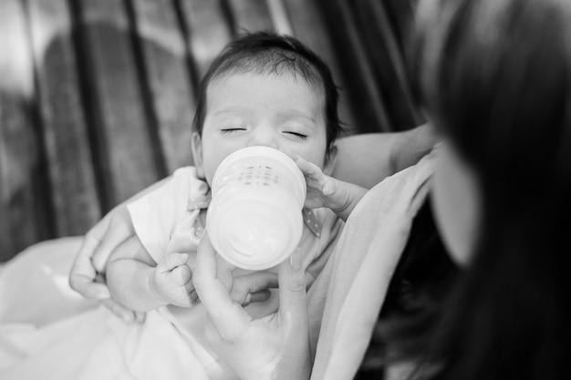 Alimentação do bebê por uma mistura de laticínios da pequena garrafa de crianças