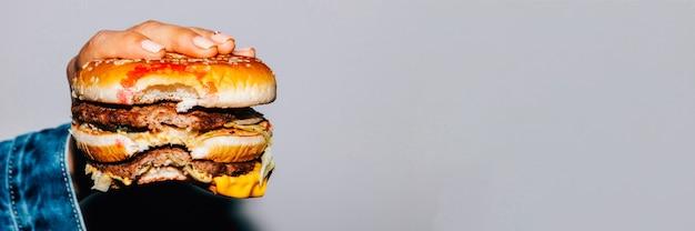 Alimentação não saudável. comida rápida. cheeseburger duplo mordido na mão feminina sobre fundo cinza.