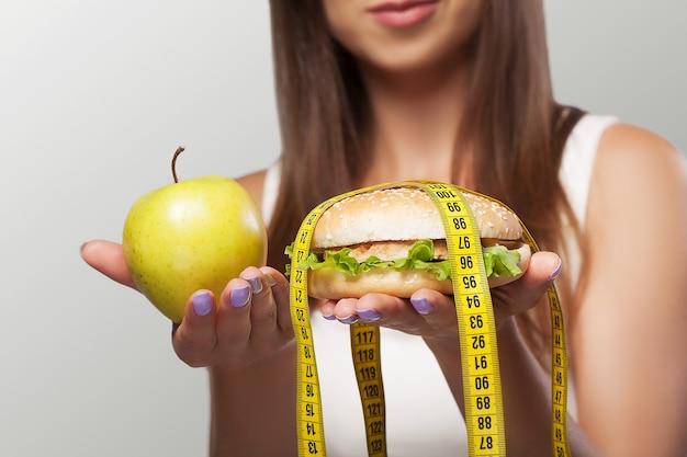 Alimentação prejudicial e saudável jovem escolhe entre alimentos prejudiciais e saudáveis dieta conceito de saúde e beleza sobre um fundo cinza.