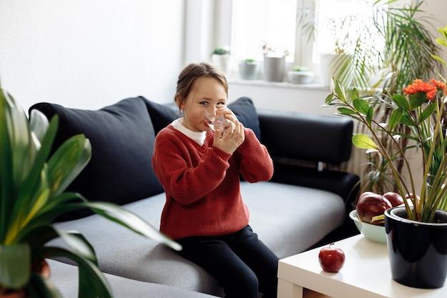 Alimentação saudável - criança segurando e bebendo um copo d'água, muitas frutas frescas na mesa em frente em casa, conceito de estilo de vida saudável