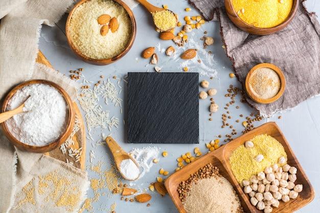 Alimentação saudável, dieta, conceito de comida equilibrada. variedade de farinha sem glúten, amêndoa, milho, arroz em uma mesa. vista superior do plano de fundo