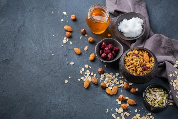 Alimentação saudável, dieta e nutrição, fitness, alimentação equilibrada, conceito de café da manhã. muesli de granola caseiro com ingredientes em uma mesa. copie o fundo do espaço