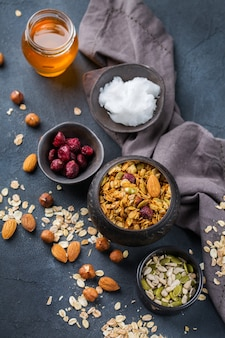Alimentação saudável, dieta e nutrição, fitness, alimentação equilibrada, conceito de café da manhã. muesli de granola caseiro com ingredientes em uma mesa.