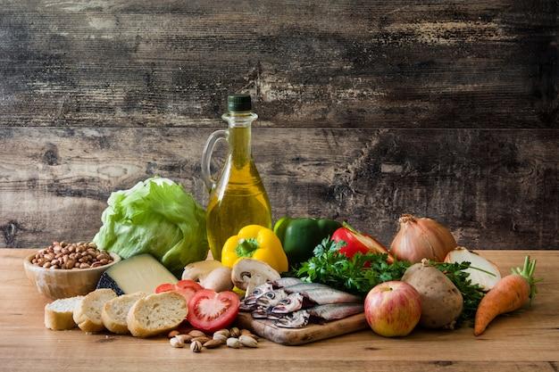 Alimentação saudável. dieta mediterrânea fruitvegetables grão nozes azeite e peixe na mesa de madeira.