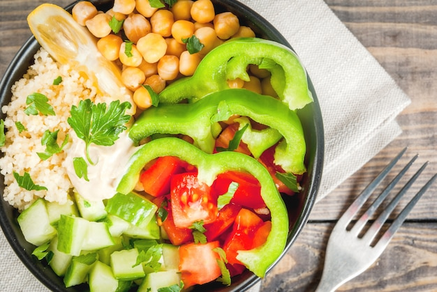 Alimentação saudável, dieta. tigela de buda vegetariana vegetal - cuscuz (quinoa), grão de bico, tomate, abobrinha (pepino), pimenta, hummus, limão e verduras. na mesa de madeira, com água, vista superior perto