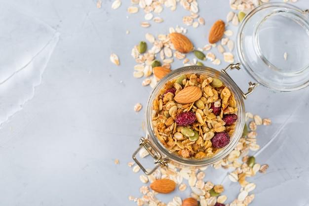 Alimentação saudável e limpa, dieta e nutrição, aptidão, alimentação equilibrada, conceito de café da manhã. muesli de granola caseiro com ingredientes em uma mesa. vista superior do plano de fundo do espaço da cópia