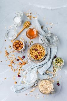 Alimentação saudável e limpa, dieta e nutrição, aptidão, alimentação equilibrada, conceito de café da manhã. muesli de granola caseiro com ingredientes em uma mesa. vista superior do plano de fundo