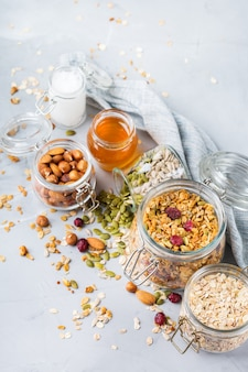 Alimentação saudável e limpa, dieta e nutrição, aptidão, alimentação equilibrada, conceito de café da manhã. muesli de granola caseiro com ingredientes em uma mesa