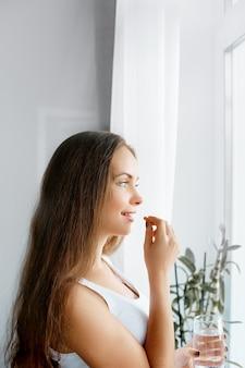 Alimentação saudável, estilo de vida. close-up de uma mulher sorridente e feliz tomando pílula