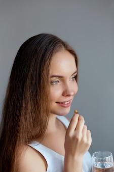 Alimentação saudável, estilo de vida. feche de mulher sorridente feliz tomando pílula de vitamina com óleo de fígado de bacalhau ômega-3 e segurando um copo de água doce pela manhã.