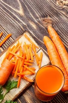 Alimentação saudável - fatiado de cenoura e suco de cenoura em fundo de madeira.