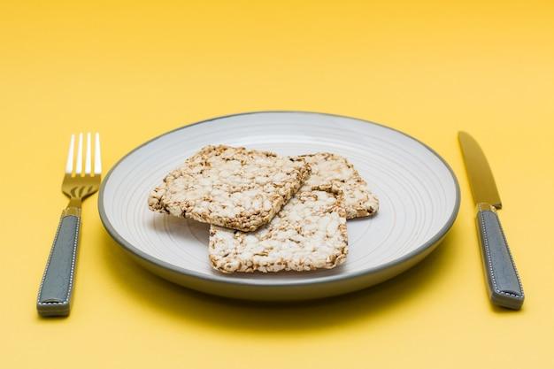 Alimentação saudável. pão crocante feito de aveia, trigo, linhaça e sementes de gergelim em um prato e talheres em um fundo amarelo