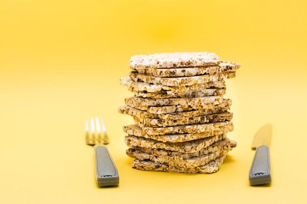 Alimentação saudável. pão crocante feito de aveia, trigo, linho e sementes de gergelim em uma pilha e talheres sobre fundo amarelo superalimento