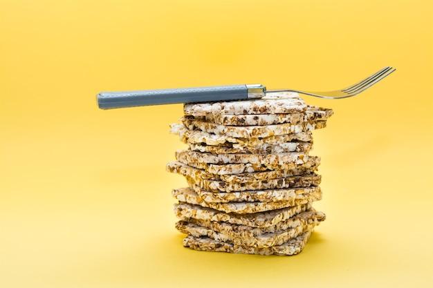 Alimentação saudável. pão estaladiço feito de aveia, trigo, linho e sementes de gergelim em uma pilha e um garfo sobre ele em um fundo amarelo. superalimento