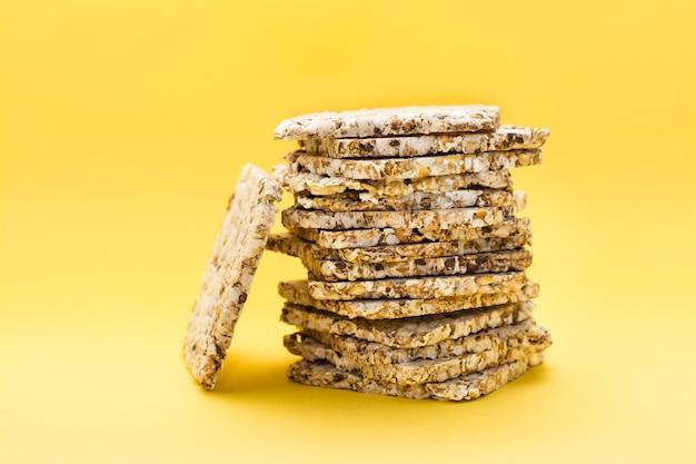 Alimentação saudável. pão estaladiço feito de aveia, trigo, linho e sementes de gergelim em uma pilha sobre um fundo amarelo. superalimento