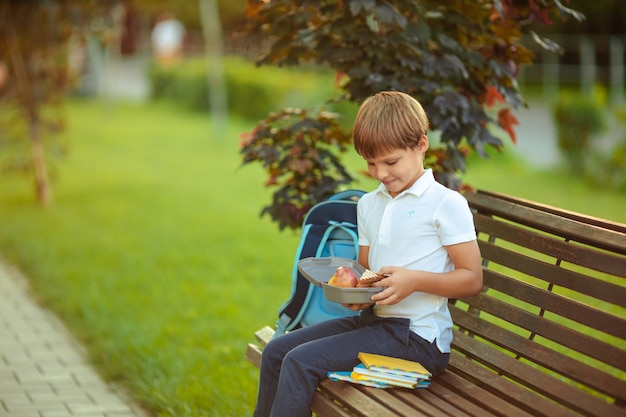 Alimentação saudável para o aluno. menino bonito comendo frutas ao ar livre, perto da escola.