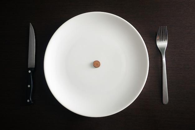 Alimentação saudável, pobreza, economizando moedas de dinheiro em um prato branco na sala de jantar.