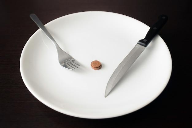 Alimentação saudável, pobreza, economizando moedas de dinheiro em um prato branco.
