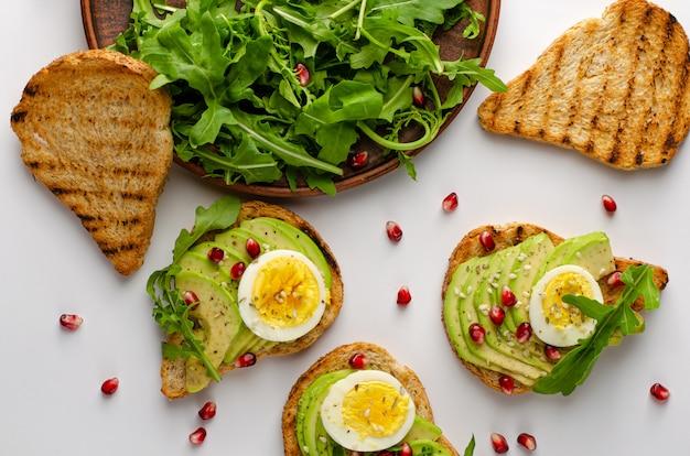 Alimentação saudável. torradas de abacate com ovo, salada de rúcula e sementes de romã. vista superior, plana