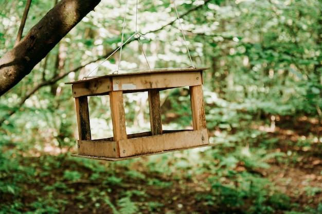 Alimentador de pássaros de madeira em uma floresta verde de verão ou no parque da cidade