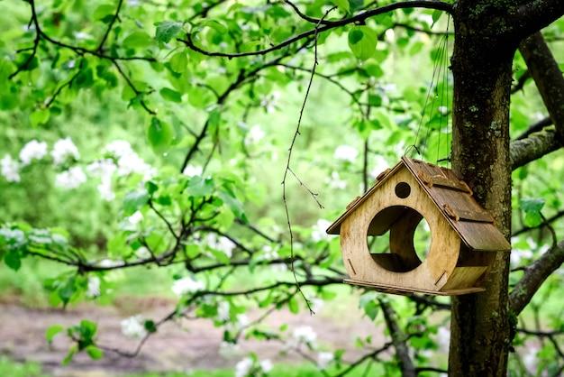 Alimentador de pássaros de madeira pendurado em uma macieira em flor no pomar