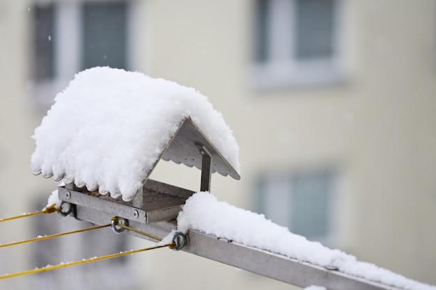 Alimentador do pássaro no inverno com neve.