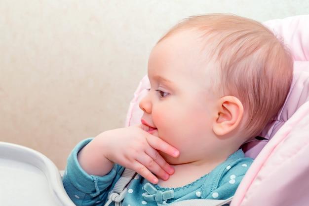 Alimentando o bebê fofo no carrinho com colher