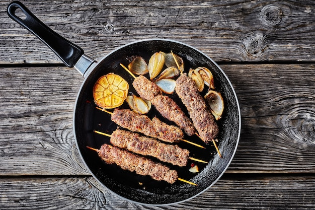 Alimento da dieta keto: kofta kebab de carne de cordeiro picada assada no forno em espetos com especiarias em uma frigideira