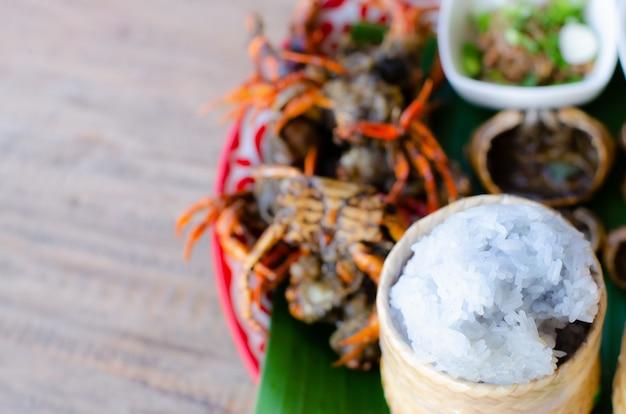 Alimento de caranguejo picante quente do estilo tailandês e arroz colorido na bandeja.