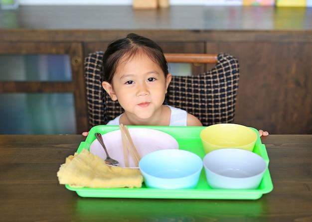 Alimento de espera da menina asiática pequena na tabela com muitos bacia vazia.