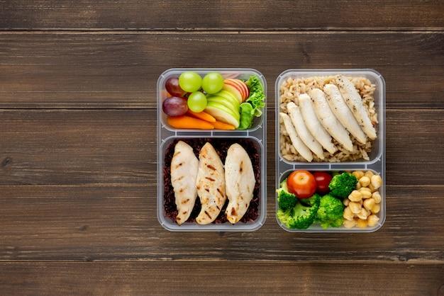 Alimento rico em nutrientes saudável com baixo teor de gordura em conjuntos de caixa de refeição para viagem na vista superior do plano de fundo de madeira com espaço de cópia