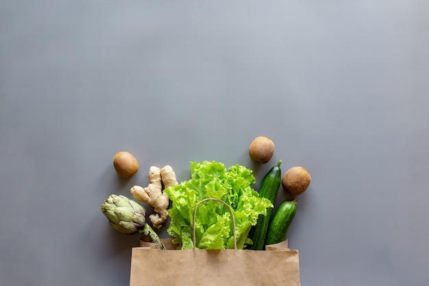 Alimento saudável e orgânico flay conceito leigo. saco ecológico com folhas de salada de alface espalhadas, kiwi, kiwi, pepino, alcachofra e raiz de gengibre.