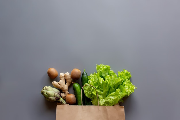 Alimento saudável e orgânico flay conceito leigo. saco ecológico reutilizável com folhas de salada de alface, kiwi, pepino, alcachofra e raiz de gengibre.