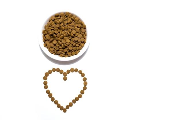 Alimento seco para cães e gatos em uma tigela branca. coração com a comida. fundo branco do estúdio. foto de alta qualidade