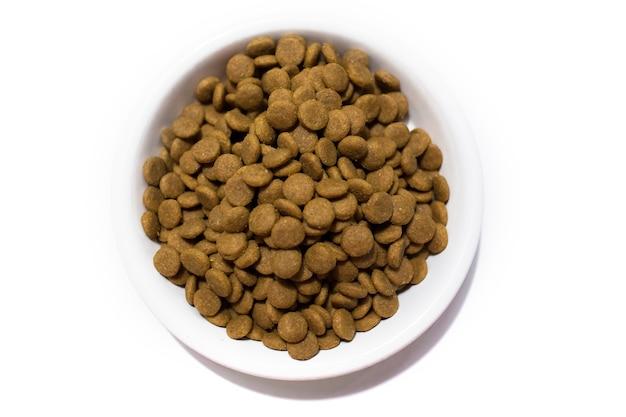 Alimento seco para cães e gatos em uma tigela branca. fundo branco do estúdio. foto de alta qualidade