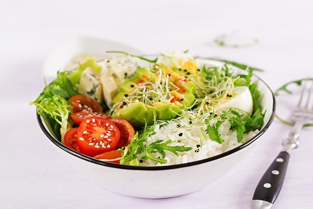 Alimento verde saudável da bacia de buddha do vegetariano com ovos, arroz, tomate, abacate e queijo azul na tabela.