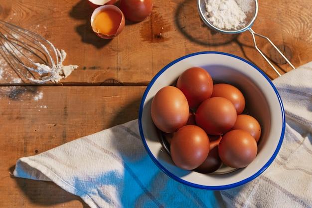 Alimentos crus, farinha e ovos para fazer a massa na mesa de madeira.