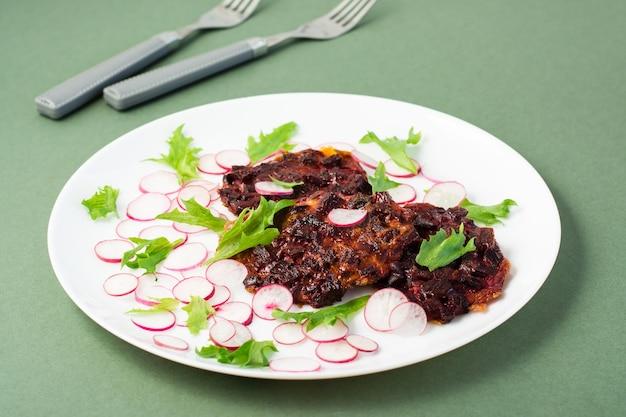 Alimentos de dieta vegetal. bife de beterraba, rabanete e folhas de salada frisada em um prato sobre uma mesa verde