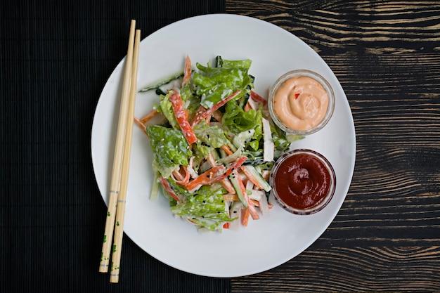 Alimentos dietéticos, salada de vegetais frescos com imitação de vara de caranguejo, temperado com molho de soja e gergelim japonês.