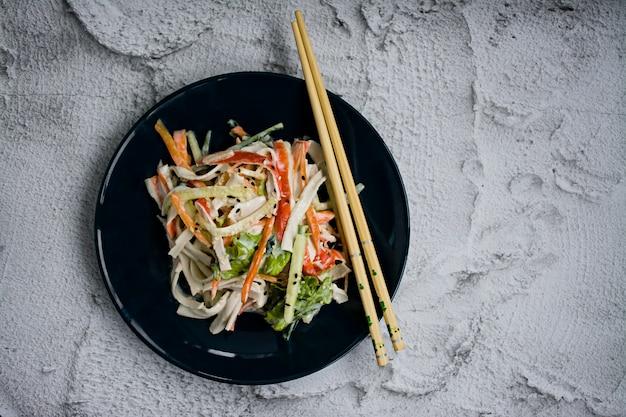 Alimentos dietéticos, salada de vegetais frescos com imitação de vara de caranguejo