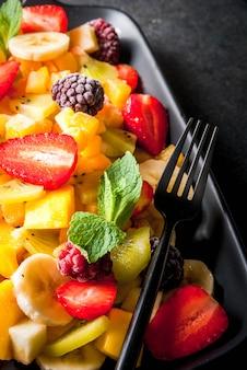 Alimentos dietéticos veganos. vitaminas. sobremesa. verão. salada de frutas orgânicas frescas manga, pêssego, maçã, banana, kiwi, morango, amoras. na placa de cerâmica preta, espaço de cópia de mesa de pedra preta