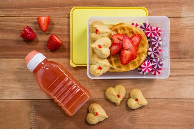 Alimentos doces e suco em caixa de almoço
